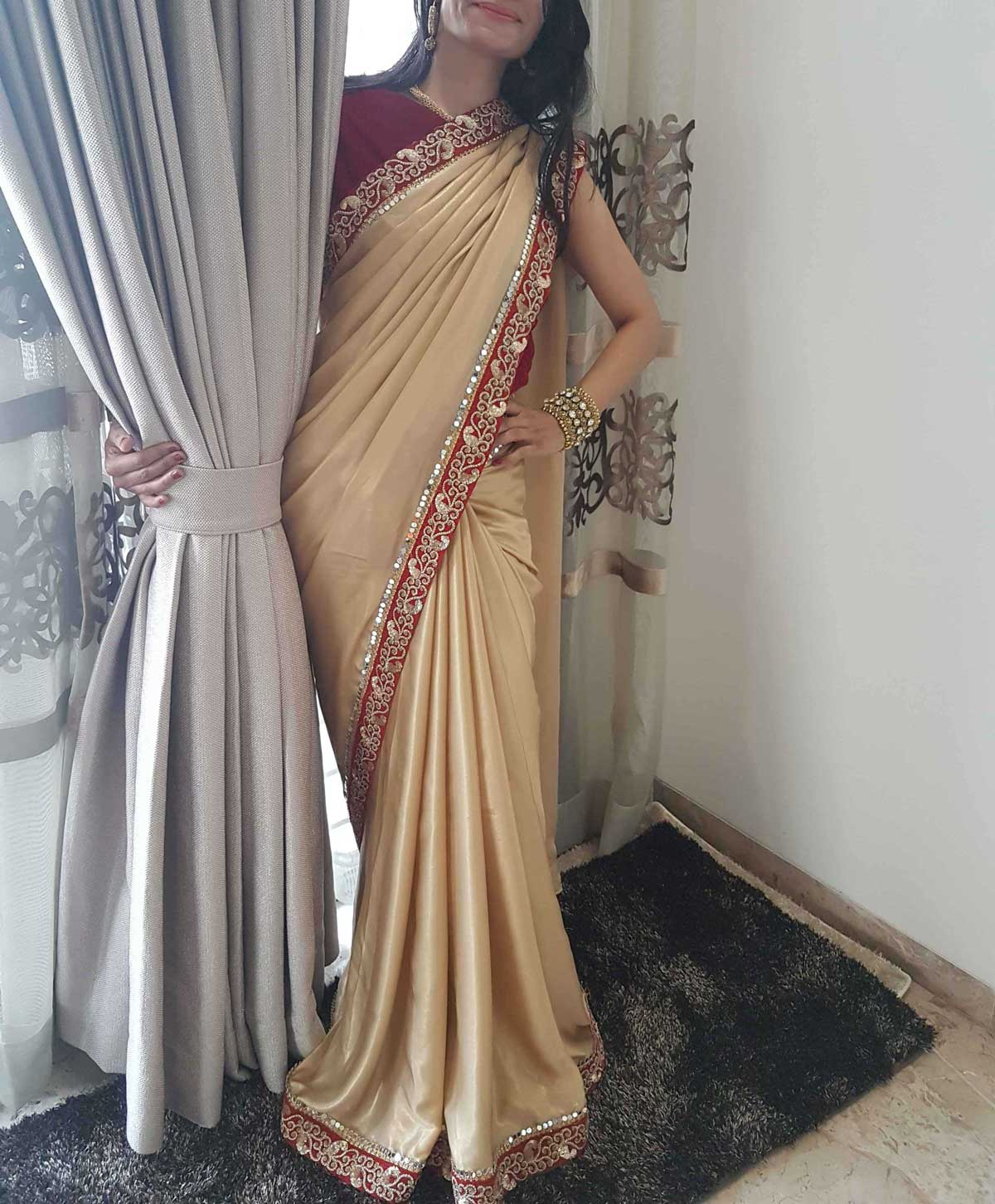 A Beautiful and Elegant Golden Saree with Red Mirror Work and Weaved Border with a Blouse in Maroon Velvet