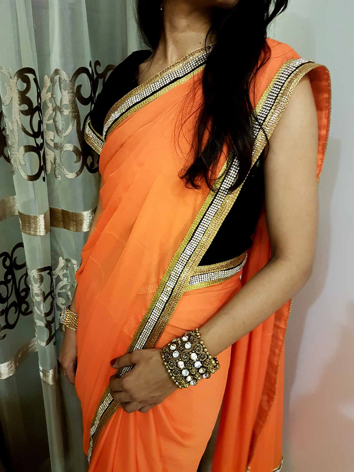 Georgette Saree in Orange with Stone and Golden Borders and Black Velvet Blouse