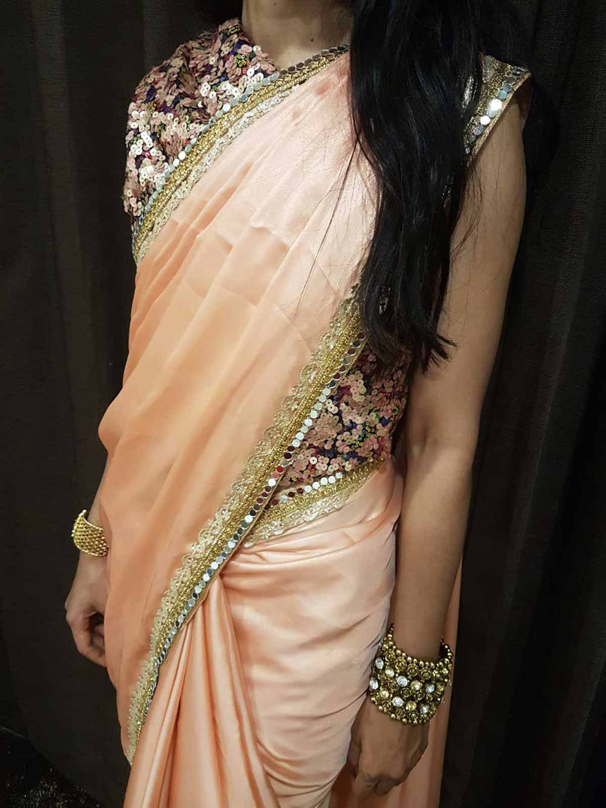 Peach Saree with Mirror Work and Gota Patthi Borders paired up with a Multi colored Sequence Blouse
